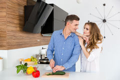 Bitande grönsaker för härliga par på köket Royaltyfria Bilder
