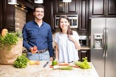 Bitande grönsaker för latinamerikanska par i kök arkivbild
