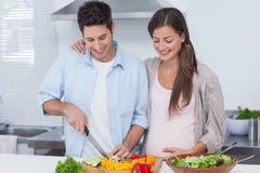 Bitande grönsaker för man bredvid hans preganant partner Arkivfoton