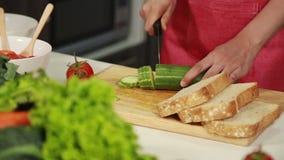Bitande gurka för hand ombord i kökrum stock video