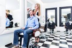 Bitande hår för frisör av kunden Royaltyfri Fotografi
