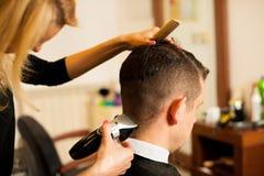 Bitande hår för kvinnlig frisör av att le manklienten på skönhet arkivfoton