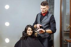 Bitande hår för yrkesmässig manlig frisör till en kvinnlig klient på designsalongen Arkivfoto