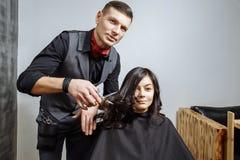 Bitande hår för yrkesmässig manlig frisör till en kvinnlig klient på designsalongen Arkivbild