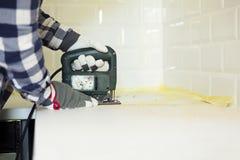 Bitande kökcountertop för man genom att använda den elektriska figursågen Hem- impro royaltyfri bild