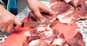 Bitande kött med en kniv royaltyfri foto