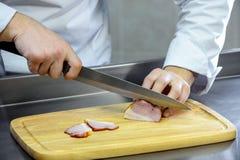 Bitande kött med en kniv på ett träbräde Arkivfoto