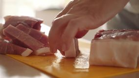 Bitande kött på ett plast- kökbräde Kvinnlighandnärbilden klippte köttskivor med en kniv stock video