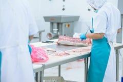 Bitande köttslakthusarbetare i fabriken Arkivfoton