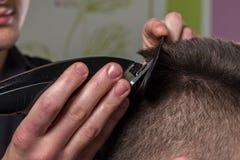 Bitande klienthår för frisör med en elektrisk hårclipper arkivfoto