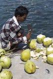 Bitande kokosnötter för en oidentifierad man Royaltyfri Foto