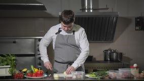Bitande lök för ung kock på en vit skärbrädacloseup Matlagning i ett restaurangkök stock video