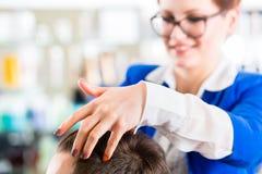 Bitande manhår för frisör i frisersalong Royaltyfri Fotografi