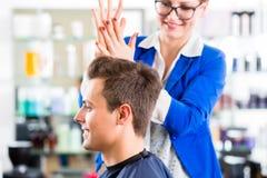 Bitande manhår för frisör i frisersalong Fotografering för Bildbyråer