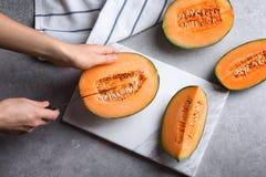 Bitande melon för kvinna på tabellen royaltyfria foton