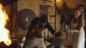 Bitande metall vid handsmidet med hjälp av två personer stock video