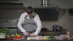 Bitande morötter för ung kock på en vit skärbrädacloseup Matlagning i ett restaurangkök arkivfilmer