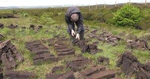 Bitande och passande torvatorv med en spade i mossamyr i Irland lager videofilmer