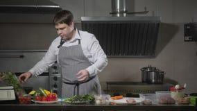 Bitande paprika för ung kock på en vit skärbrädacloseup Matlagning i ett restaurangkök lager videofilmer