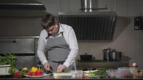 Bitande paprika för ung kock på en vit skärbrädacloseup Matlagning i ett restaurangkök stock video