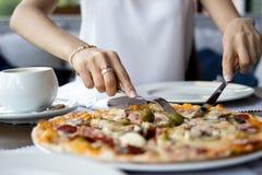 Bitande pizza för ung kvinna arkivbilder