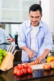 Bitande sallad för asiatisk man i kök Royaltyfri Foto
