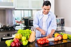 Bitande sallad för asiatisk man i kök Arkivbilder