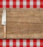 Bitande skärbräda och kökkniv Laga mat den fastställda over röda ginghambordduken Royaltyfri Foto
