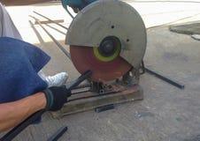 Bitande stål med maskinen för att klippa stål av arbetaren Arkivbilder