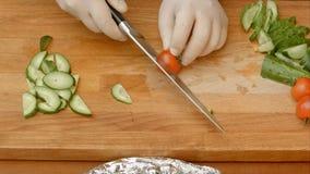 Bitande tomat för manlig kockhand på skärbräda med den skarpa kniven Royaltyfria Bilder