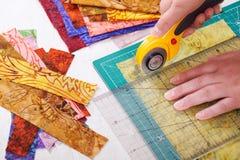 Bitande tygstycken för process vid den roterande skäraren på matt användande linjal arkivfoton
