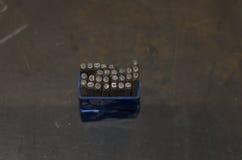 Bitar med bokstäver och nummer på metalltabellen i seminarium royaltyfria foton