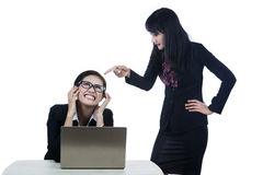 Bitchy boss isolated in white. Businesswoman yelling at her subordinate while working with her laptop Royalty Free Stock Images