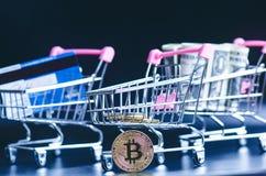 Bitcoin、银行卡和金钱在一辆台车在黑背景 购物和金钱的概念 Cryptocurrency 拟订dof重点现有量在线浅购物非常 v 免版税库存照片