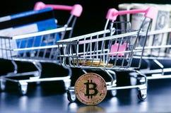 Bitcoin、银行卡和金钱在一辆台车在黑背景 购物和金钱的概念 Cryptocurrency 拟订dof重点现有量在线浅购物非常 v 免版税库存图片