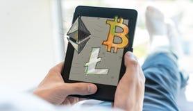 Bitcoin、Ethereum和Litecoin与使用片剂的人 图库摄影