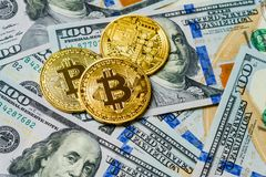 bitcoin三枚符号硬币在一百美元钞票的  交换一美元的bitcoin现金 免版税库存照片