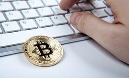 bitcoin和人的手一枚金黄硬币在膝上型计算机键盘 图库摄影