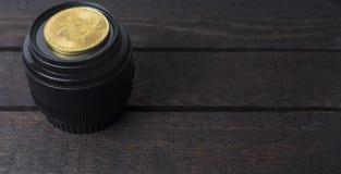 Bitcoin和摄象机镜头在木背景放置 库存照片