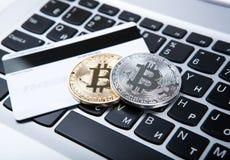 bitcoin和银行卡两枚硬币在膝上型计算机键盘 免版税图库摄影