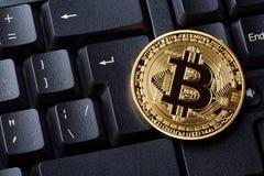 Bitcoin在个人计算机的键盘的cryptocurrency硬币 黑色接近的耳机图象软绵绵地查出话筒填充白色 隐藏货币-网银行的电子真正金钱 库存图片