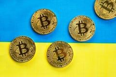 Bitcoin在乌克兰的旗子的金子颜色 免版税库存图片