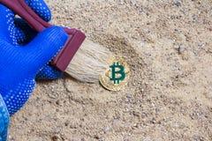 Bitcoin在沙子的考古学硬币 免版税库存图片