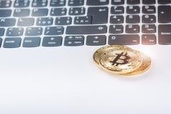 Bitcoin在白色膝上型计算机键盘铸造  计算机 投资情况 新的真正货币 多数可贵的cryptocurrency 图库摄影