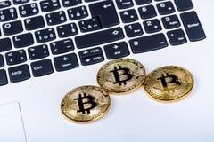 Bitcoin在白色膝上型计算机键盘铸造  计算机 投资情况 新的真正货币 多数可贵的cryptocurrency 库存照片