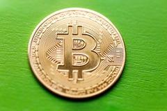 Bitcoin在绿色木背景的金币 库存图片