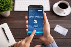 Bitcoin在被隔绝的智能手机屏幕上的收入应用 免版税库存图片