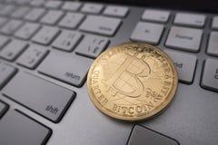Bitcoin在键盘的纪念品硬币 库存照片