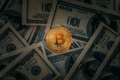Bitcoin概念 在现金金钱美元黑暗的背景的金黄Bitcoin硬币  图库摄影