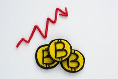 bitcoin率的减少,堆硬币和由彩色塑泥做的箭头图表 免版税库存照片